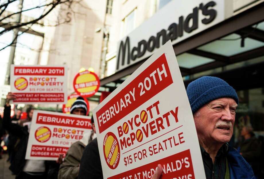Retired minister John-Otto Liljenstolpe, right, joins a crowd of Working Washington supporters protesting for 15 dollar minimum wage in front of McDonald's on 3rd Avenue and Pine Street Thursday, Feb. 20, 2014, in downtown Seattle. Seattle City Council member Kshama Sawant joined in to speak, amongst others. Photo: JORDAN STEAD, SEATTLEPI.COM / SEATTLEPI.COM