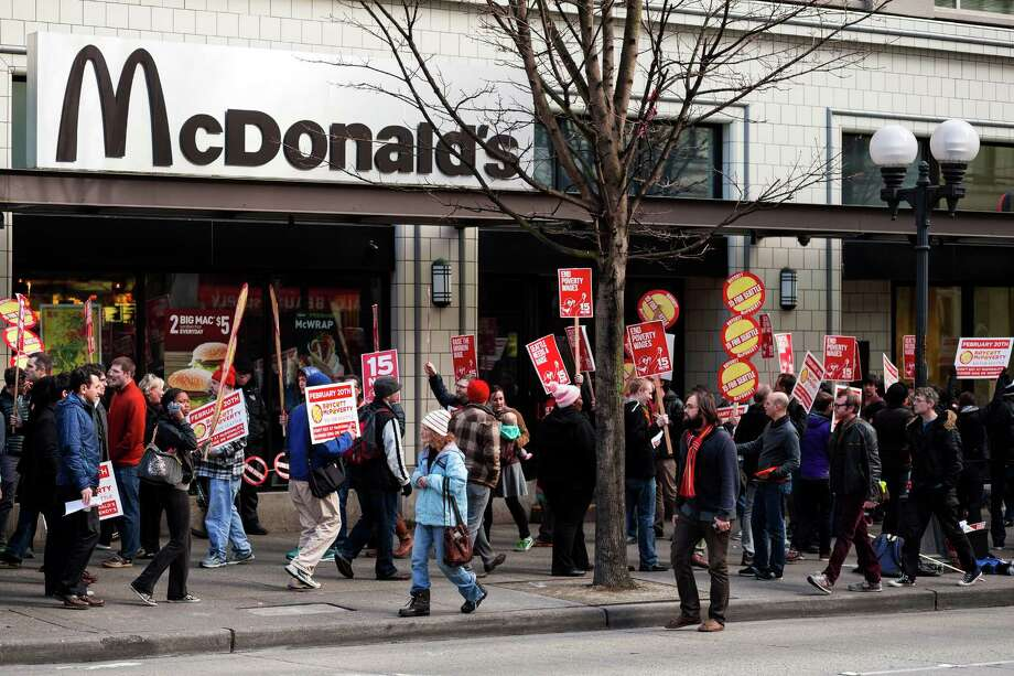 A crowd of Working Washington supporters protesting for 15 dollar minimum wage took to the space in front of McDonald's on 3rd Avenue and Pine Street to hoist signs and chant for improved pay Thursday, Feb. 20, 2014, in downtown Seattle. Seattle City Council member Kshama Sawant joined in to speak, amongst others. Photo: JORDAN STEAD, SEATTLEPI.COM / SEATTLEPI.COM