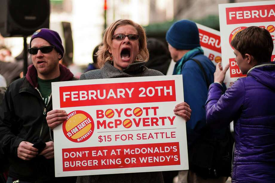 Sterling Harders, center, leads a crowd of Working Washington supporters to protest for 15 dollar minimum wage in front of McDonald's on 3rd Avenue and Pine Street Thursday, Feb. 20, 2014, in downtown Seattle. Seattle City Council member Kshama Sawant joined in to speak, amongst others. Photo: JORDAN STEAD, SEATTLEPI.COM / SEATTLEPI.COM