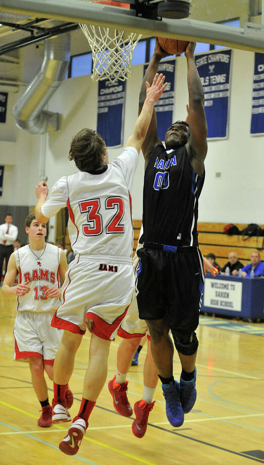 Darien's Chima Azuonwu dunks the ball on New Canaan's Erik Jager during their basketball game at Darien High School in Darien, Conn., on Thursday, Feb. 20, 2014. Darien won, 40-37. Photo: Jason Rearick / Stamford Advocate