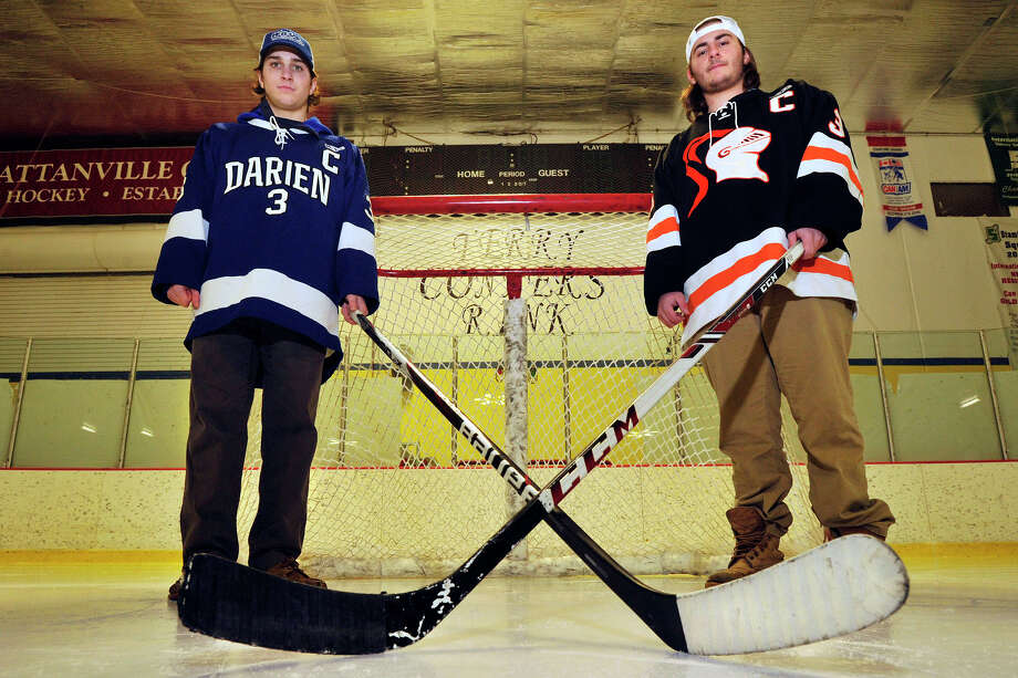 Tom Watters, left, a Darien High School hockey player, and his cousin, Billy Santora, a Stamford High School hockey player, pose for a photograph on the ice at Terry Conners Rink in Stamford, Conn., on Thursday, Feb. 20, 2014. Photo: Jason Rearick / Stamford Advocate