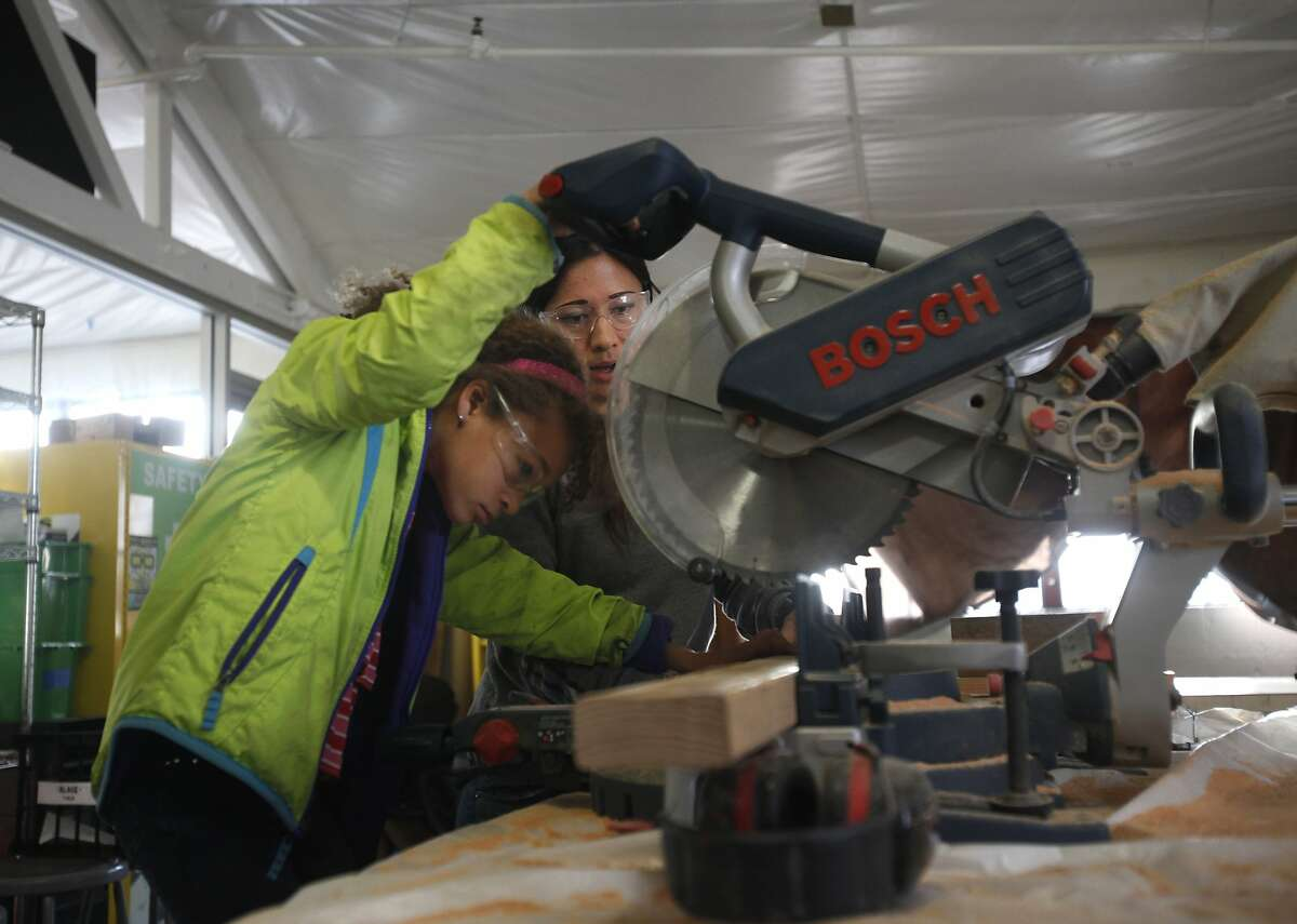 Mikaela James, 9, left, is supervised by Emily Pilloton while using a miter saw during Camp H