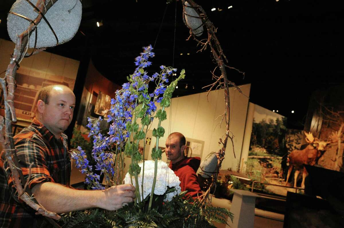 Floral designer Donald Bennett, left, with the assistance of his husband Corey Bennett builds a display as the 23rd Annual New York in Bloom is set up at the New York State Museum on Thursday, Feb. 20, 2014, in Albany, N.Y. (Michael P. Farrell/Times Union)