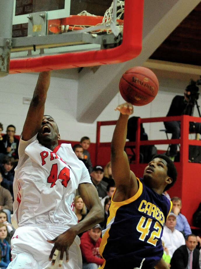 Fairfield Prep's Pascal Chukwa reacts as he slam dunks the ball, during boys basketball action against Career of New Haven in Fairfield, Conn. on Thursday February 20, 2014. At right is Career's Alden Singley. Photo: Christian Abraham / Connecticut Post