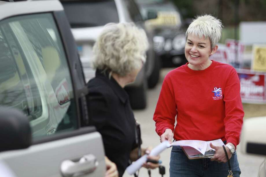 Pat Tibbs, left, president of the breakaway Montgomery County Tea Party, and Julie Turner, who heads the established Texas Patriots PAC, speak to early voters this week outside the South County Community Center in The Woodlands. Photo: Melissa Phillip, Staff / © 2014  Houston Chronicle