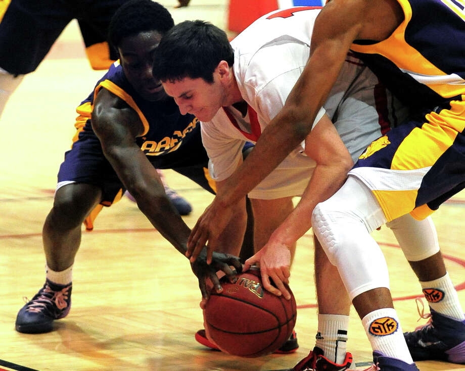 Fairfield Prep's Ray Featherston tries to retain control of the ball as Career of New Haven's Tyrell Eaddy, left, and teammate Tyreek Perkins reach in to steal, during boys basketball action in Fairfield, Conn. on Thursday February 20, 2014. Photo: Christian Abraham / Connecticut Post