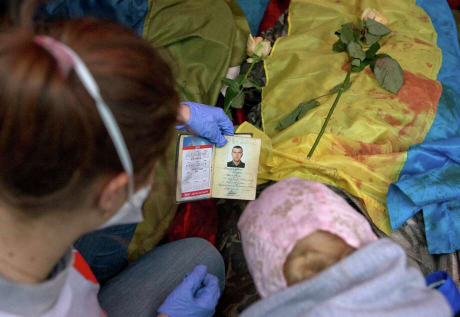 A paramedic looks at the identification document of a killed anti-government protester, in central Kiev, Ukraine, Thursday, Feb. 20, 2014. A brief truce in Ukraine's embattled capital failed Thursday, spiraling into fierce clashes between police and anti-government protesters. (AP Photo/Darko Bandic) ORG XMIT: XDB111 Photo: Darko Bandic / AP
