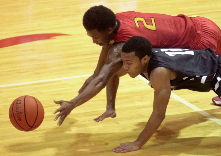 Yates guard Damion Lewis and Huffman guard Darion Gray dive for a loose ball during the first half o