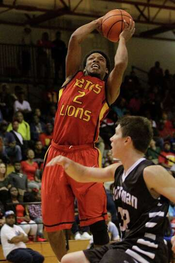 Yates guard Damion Lewis (2) takes a shot during the first half of a high school basketball game aga
