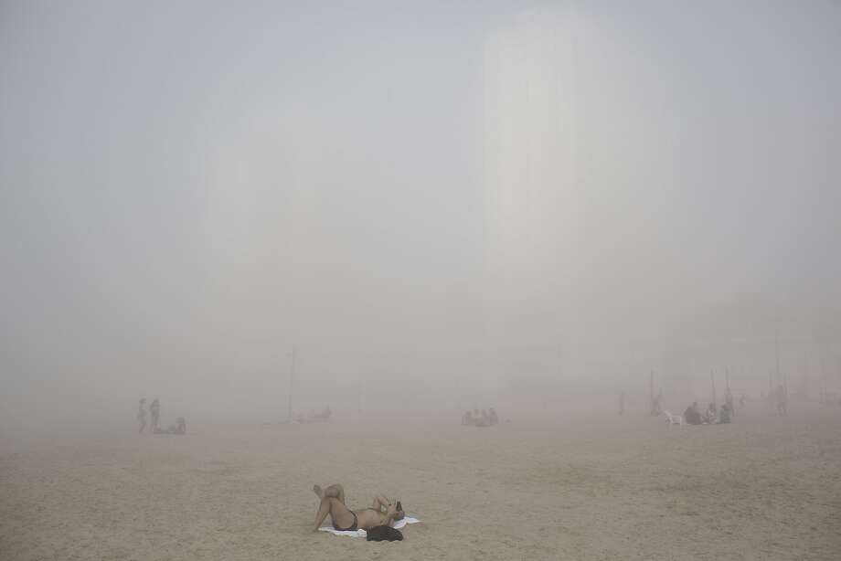 Misty Mediterranean morning: A heavy fog makes catching rays on this beach in Tel Aviv next to impossible. Photo: Oded Balilty, Associated Press