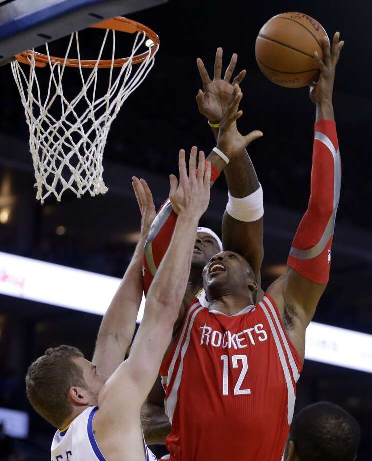 Dwight Howard (12) shoots over David Lee, left, and Jermaine O'Neal. Photo: Ben Margot, Associated Press