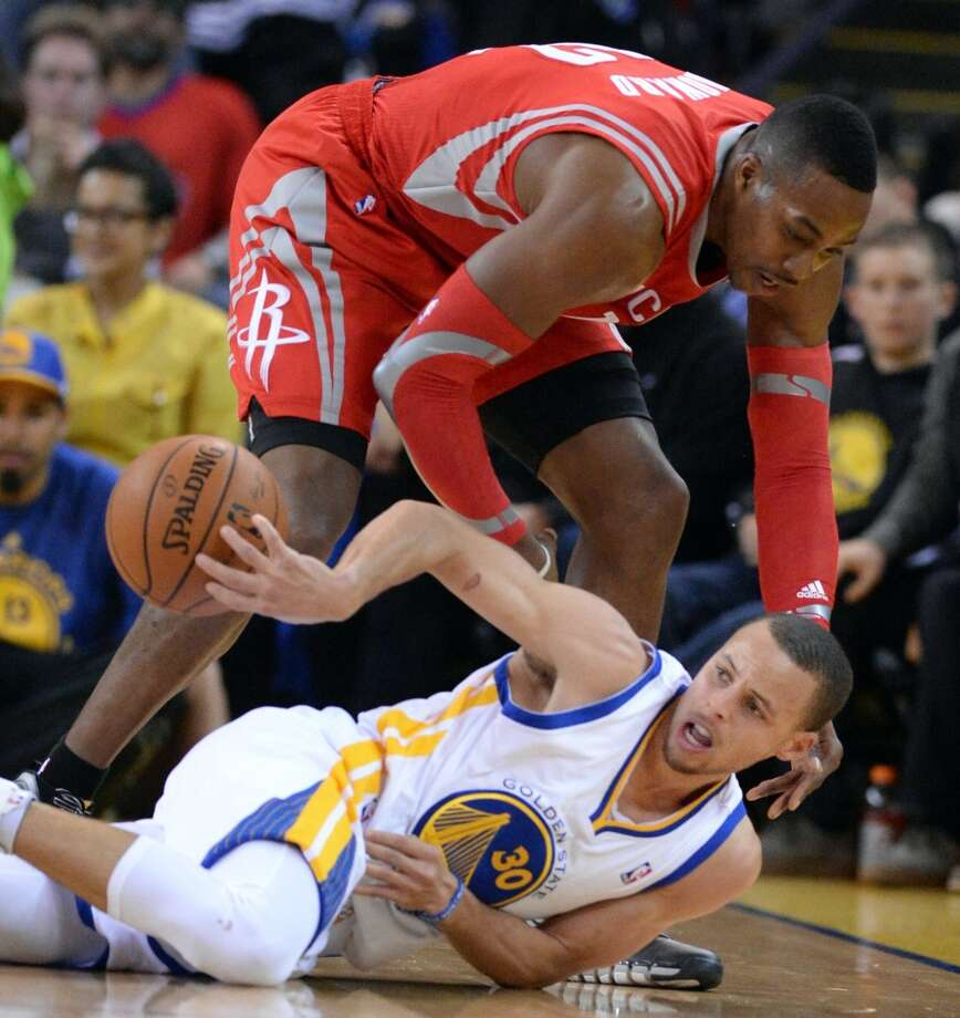 Stephen Curry, bottom, passes the ball to an open teammate as Dwight Howard looms. Photo: Doug Duran, McClatchy-Tribune News Service