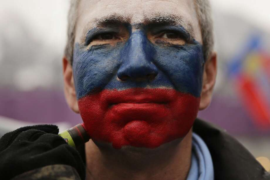 Kamil Aizetulin gets his face painted in the colors of the Russian flag during a women's ski cross seeding run at the Rosa Khutor Extreme Park, the 2014 Winter Olympics, Friday, Feb. 21, 2014, in Krasnaya Polyana, Russia.  Photo: Jae C. Hong, Associated Press