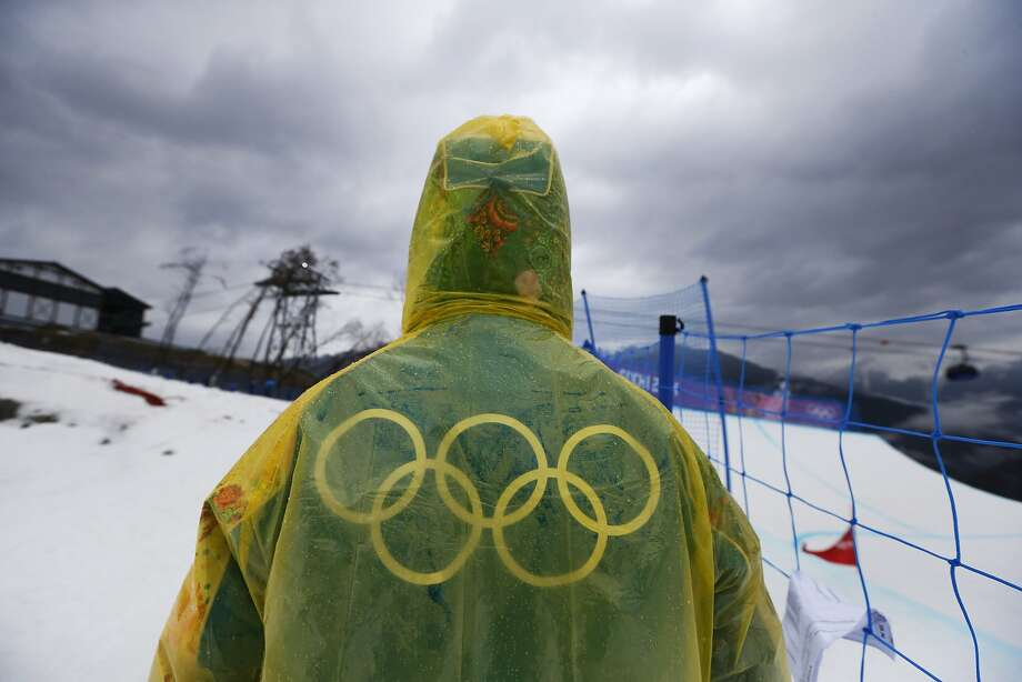 A volunteer walks beside the ski cross track during women's ski cross seeding runs, on a rainy day at the Rosa Khutor Extreme Park, at the 2014 Winter Olympics, Friday, Feb. 21, 2014, in Krasnaya Polyana, Russia.  Photo: Sergei Grits, Associated Press