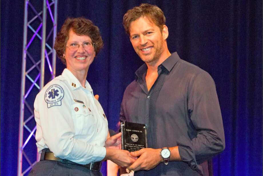 New Canaan EMS Capt. Nancy Upton receives an award from Harry Connick Jr. at a concert honoring first responders at New Canaan High School Sunday, Sept. 29, 2013. Connick, a New Canaan resident, performed as part of a fundraiser for Staying Put in New Canaan.