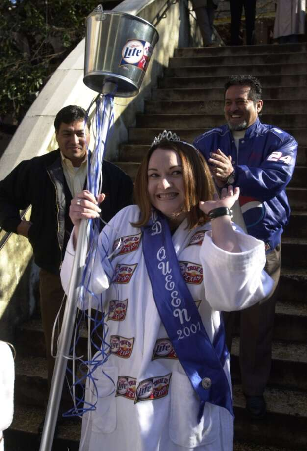 The newly crowned 2001 Mud Festival Queen, JoNeen Garcia (cq), smiles Friday morning Jan. 19, 2001 after getting her official tiara and bathrobe while Mud Festival king candidates Fred Arias, left, and Bobby Maldonado wait behind Garcia for the announcment of their title. Arias was named 2001 Mud Festival King. Photo: SAN ANTONIO EXPRESS-NEWS