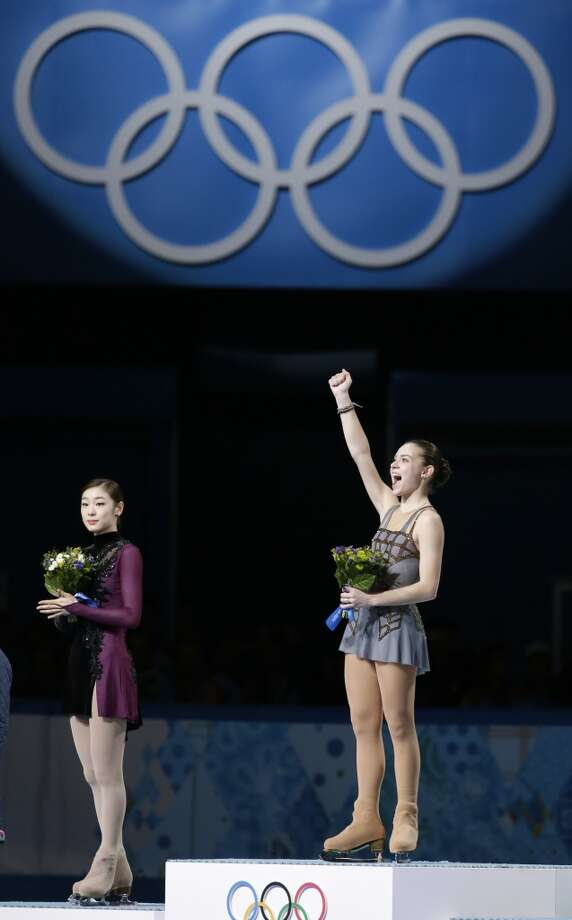 Adelina Sotnikova of Russia, right, celebrates as she stand on the podium alongside Yuna Kim of South Korea, left, during the flower ceremony for the women's free skate figure skating finals at the Iceberg Skating Palace during the 2014 Winter Olympics, Thursday, Feb. 20, 2014, in Sochi, Russia. Sotnikova placed first, followed by Kim and Kostner. (AP Photo/Bernat Armangue) Photo: Bernat Armangue, Associated Press
