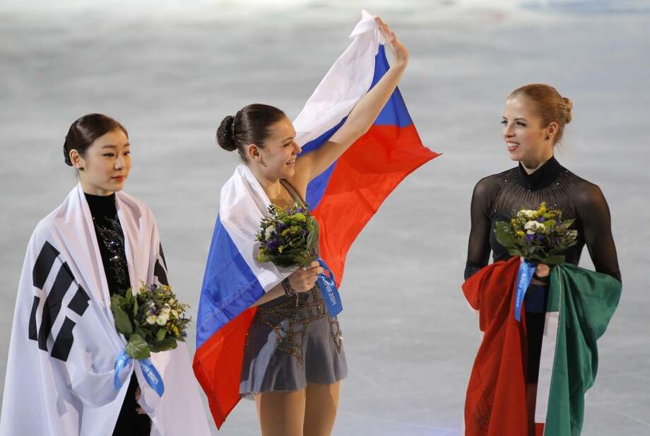 Adelina Sotnikova of Russia, centre, Yuna Kim of South Korea, left, and Carolina Kostner of Italy celebrate with their national flags as they pose for photographers following the flower ceremony for the women's free skate figure skating final at the Iceberg Skating Palace during the 2014 Winter Olympics, Thursday, Feb. 20, 2014, in Sochi, Russia. Sotnikova placed first, followed by Kim and Kostner. (AP Photo/Vadim Ghirda) Photo: Vadim Ghirda, Associated Press