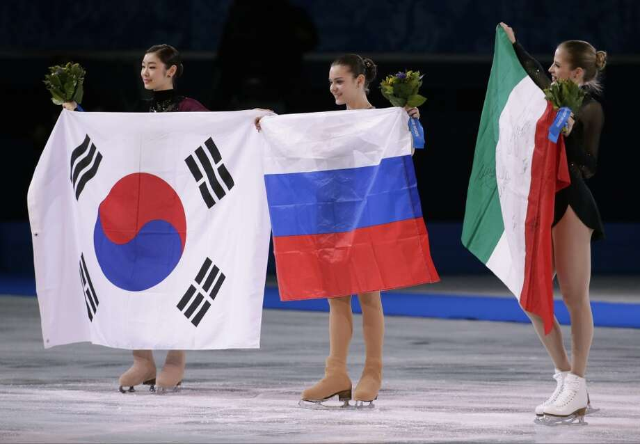 Adelina Sotnikova of Russia, centre, Yuna Kim of South Korea, left, and Carolina Kostner of Italy celebrate with their national flags as they pose for photographers following the flower ceremony for the women's free skate figure skating final at the Iceberg Skating Palace during the 2014 Winter Olympics, Thursday, Feb. 20, 2014, in Sochi, Russia. Sotnikova placed first, followed by Kim and Kostner. (AP Photo/Bernat Armangue) Photo: Bernat Armangue, Associated Press