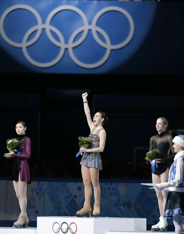 Adelina Sotnikova of Russia, centre, celebrates alongside Yuna Kim of South Korea, left, and Carolina Kostner of Italy as they stand on the podium during the flower ceremony for the women's free skate figure skating final at the Iceberg Skating Palace during the 2014 Winter Olympics, Thursday, Feb. 20, 2014, in Sochi, Russia. (AP Photo/Bernat Armangue) Photo: Bernat Armangue, Associated Press