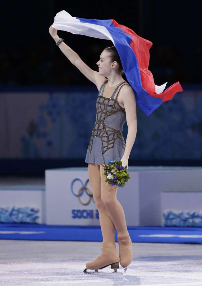 Adelina Sotnikova of Russia celebrates with the national flag after winning the women's free skate figure skating finals at the Iceberg Skating Palace during the 2014 Winter Olympics, Thursday, Feb. 20, 2014, in Sochi, Russia. (AP Photo/Bernat Armangue) Photo: Bernat Armangue, Associated Press