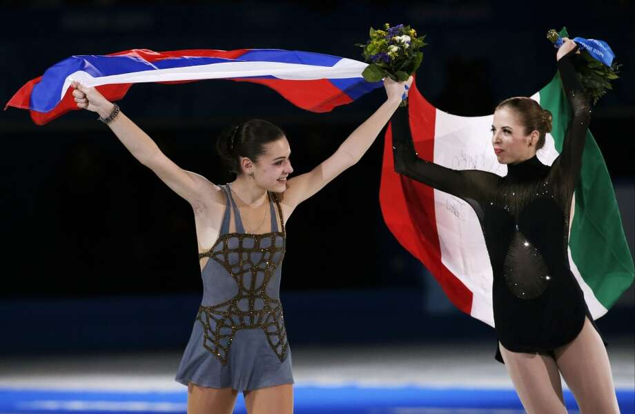Adelina Sotnikova of Russia, left, and Carolina Kostner of Italy celebrate following the flower ceremony for the women's free skate figure skating finals at the Iceberg Skating Palace during the 2014 Winter Olympics, Thursday, Feb. 20, 2014, in Sochi, Russia. Sotnikova placed first, followed by Kim and Kostner. (AP Photo/Bernat Armangue) Photo: Bernat Armangue, Associated Press
