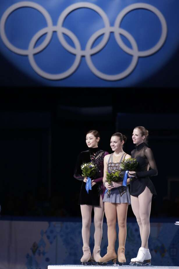 Adelina Sotnikova of Russia, centre, Yuna Kim of South Korea, left, and Carolina Kostner of Italy stand on the podium during the flower ceremony for the women's free skate figure skating final at the Iceberg Skating Palace during the 2014 Winter Olympics, Thursday, Feb. 20, 2014, in Sochi, Russia. Sotnikova placed first, followed by Kim and Kostner. (AP Photo/Bernat Armangue) Photo: Bernat Armangue, Associated Press