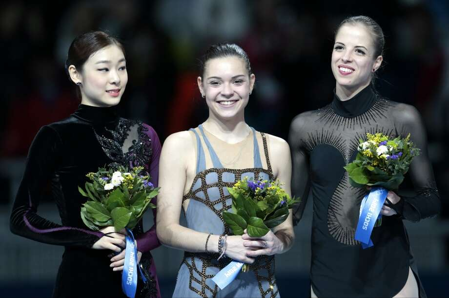 Adelina Sotnikova of Russia, centre, Yuna Kim of South Korea, left, and Carolina Kostner of Italy stand on the podium during the flower ceremony for the women's free skate figure skating final at the Iceberg Skating Palace during the 2014 Winter Olympics, Thursday, Feb. 20, 2014, in Sochi, Russia. Sotnikova placed first, followed by Kim and Kostner. (AP Photo/Ivan Sekretarev) Photo: Ivan Sekretarev, Associated Press