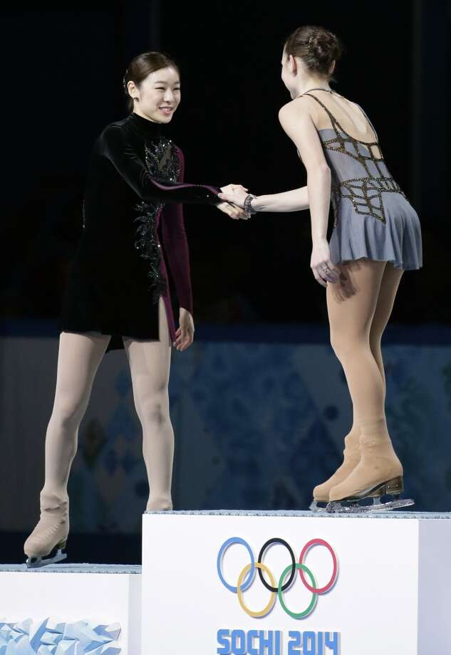 Yuna Kim of South Korea, left, shakes hands with Adelina Sotnikova of Russia as they stand on the podium during the flower ceremony for the women's free skate figure skating finals at the Iceberg Skating Palace during the 2014 Winter Olympics, Thursday, Feb. 20, 2014, in Sochi, Russia. Sotnikova placed first, followed by Kim and Kostner. (AP Photo/Bernat Armangue) Photo: Bernat Armangue, Associated Press