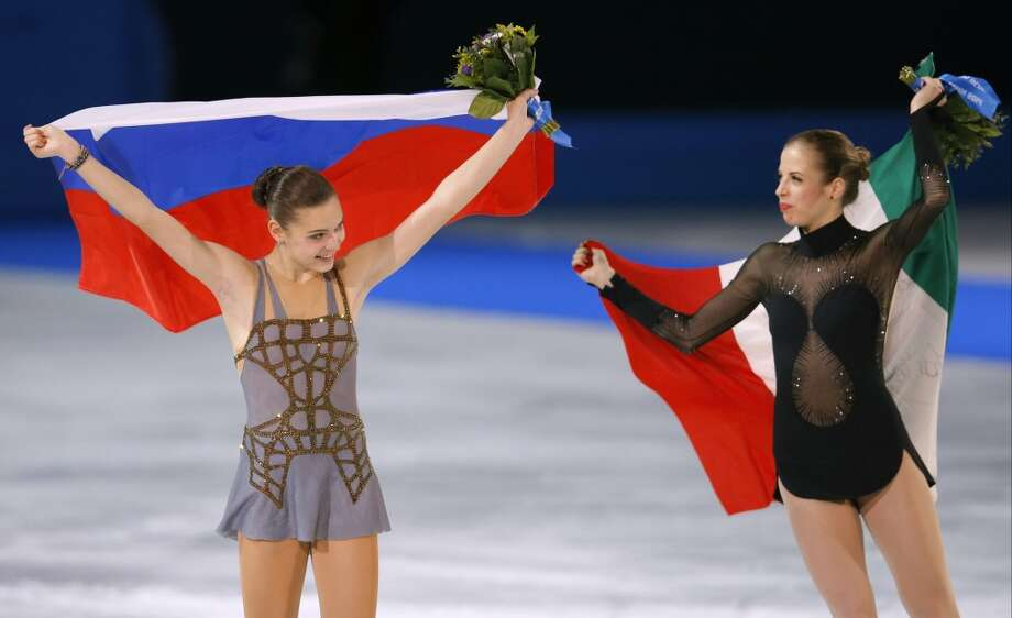 Adelina Sotnikova of Russia, left, and Carolina Kostner of Italy celebrate following the flower ceremony for the women's free skate figure skating finals at the Iceberg Skating Palace during the 2014 Winter Olympics, Thursday, Feb. 20, 2014, in Sochi, Russia. Sotnikova placed first, followed by Kim and Kostner. (AP Photo/Vadim Ghirda) Photo: Vadim Ghirda, Associated Press