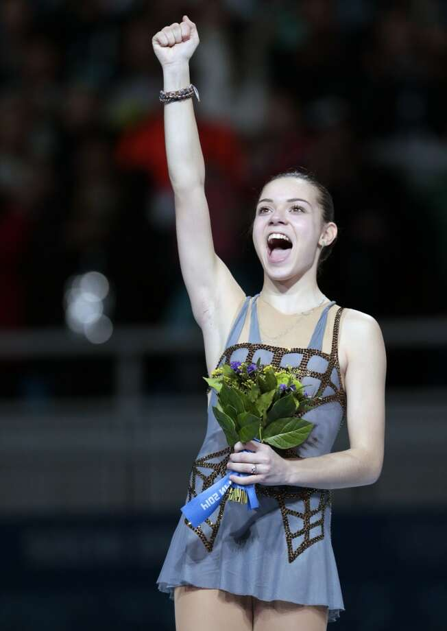 Adelina Sotnikova of Russia celebrates her first place as she stands on the podium during the flower ceremony for the women's free skate figure skating finals at the Iceberg Skating Palace during the 2014 Winter Olympics, Thursday, Feb. 20, 2014, in Sochi, Russia. (AP Photo/Ivan Sekretarev) Photo: Ivan Sekretarev, Associated Press
