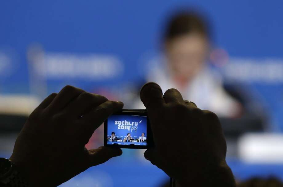 A person takes a photograph of Adelina Sotnikova of Russia, centre, Yuna Kim of South Korea, left, and Carolina Kostner of Italy as they attend a news conference following the women's free skate figure skating finals at the Iceberg Skating Palace during the 2014 Winter Olympics, Thursday, Feb. 20, 2014, in Sochi, Russia. Sotnikova placed first, followed by Kim and Kostner. (AP Photo/Darron Cummings) Photo: Darron Cummings, Associated Press