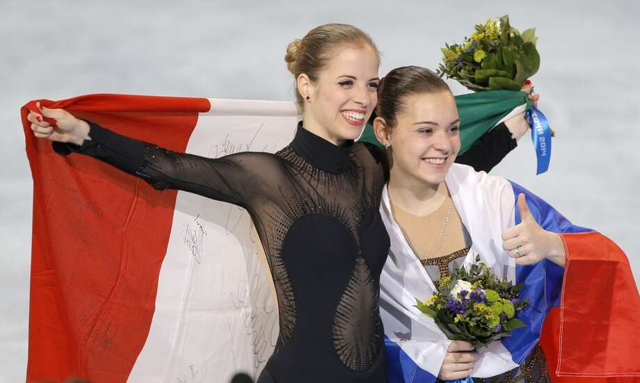 Adelina Sotnikova of Russia, right, and Carolina Kostner of Italy celebrate with their national flags as they pose for photographers following the flower ceremony for the women's free skate figure skating final at the Iceberg Skating Palace during the 2014 Winter Olympics, Thursday, Feb. 20, 2014, in Sochi, Russia. Sotnikova placed first, followed by Kim and Kostner. (AP Photo/Vadim Ghirda) Photo: Vadim Ghirda, Associated Press
