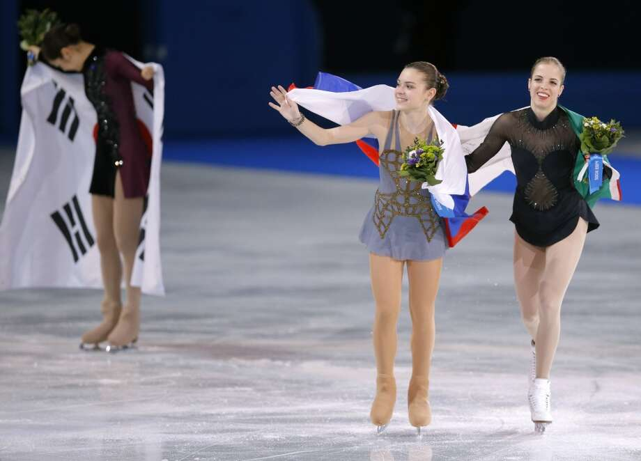 Adelina Sotnikova of Russia, centre, Carolina Kostner of Italy, right, and Yuna Kim of South Korea, left, celebrate following the flower ceremony for the women's free skate figure skating finals at the Iceberg Skating Palace during the 2014 Winter Olympics, Thursday, Feb. 20, 2014, in Sochi, Russia. Sotnikova placed first, followed by Kim and Kostner. (AP Photo/Vadim Ghirda) Photo: Vadim Ghirda, Associated Press