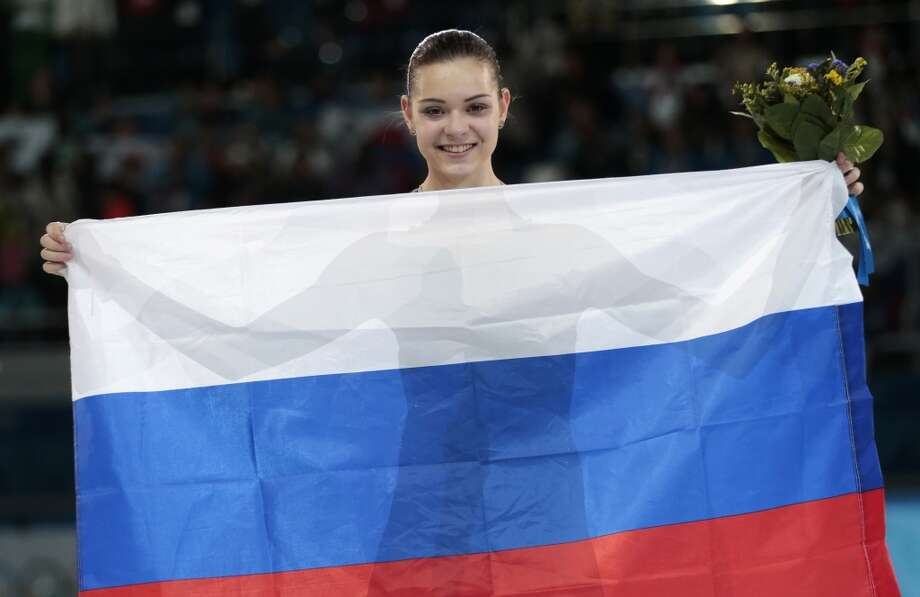 Adelina Sotnikova of Russia celebrates after placing first during the flower ceremony for the women's free skate figure skating final at the Iceberg Skating Palace during the 2014 Winter Olympics, Thursday, Feb. 20, 2014, in Sochi, Russia. Sotnikova placed first, followed by Kim and Kostner. (AP Photo/Ivan Sekretarev) Photo: Ivan Sekretarev, Associated Press
