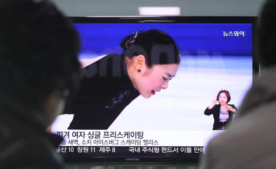"People watch a TV news showing Yuna Kim of South Korea at the women's free skate figure skating final during the 2014 Winter Olympics, at the Seoul Railway Station in Seoul, South Korea, Friday, Feb. 21, 2014. South Koreans still love Yuna Kim. The judges, however, are another matter. Kim, known as the ""Queen"" in South Korea, finished with the figure skating silver medal at the Sochi Olympics behind Adelina Sotnikova of Russia. That left many South Koreans furious over what they saw as questionable judging. (AP Photo/Ahn Young-joon) Photo: Ahn Young-joon, Associated Press"