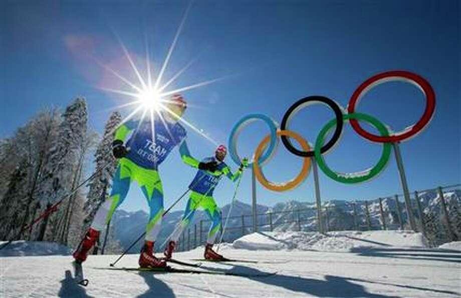 Integrantes del equipo eslovenio de esquí a campo traviesa frente a los anillos olímpicos en Krasnaya Polyana, Rusia, el domingo 2 de febrero de 2014. (AP Foto/Gero Breloer) Photo: Gero Breloer, AP / AP