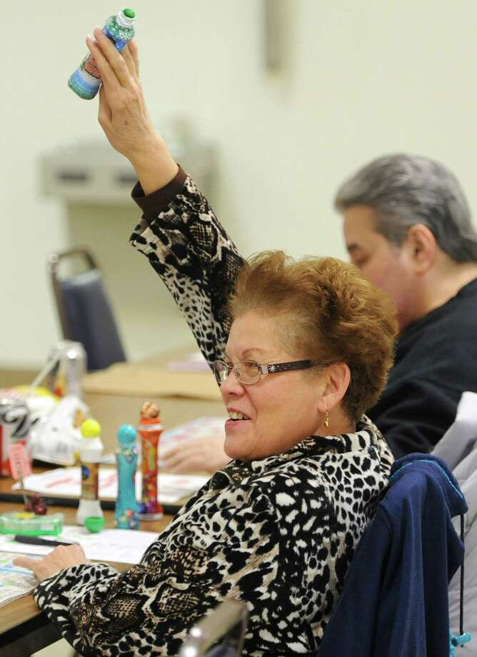 Angie Camacho, of Danbury, raises her hand after getting a Bingo at Bingo night at St. Peter Church in Danbury, Conn. Wednesday, Feb. 19, 2014.  The weekly event has been going on in the church basement since 1996 and typically draws near 100 players. Photo: Tyler Sizemore / The News-Times
