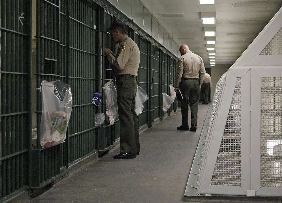 FILE - In this Oct. 3, 2012, file photo, Los Angeles County Sheriff's deputies inspect a cell block at the Men's Central Jail in downtown Los Angeles. A new federal civil rights indictment alleges that two Los Angeles County sheriff's deputies beat a handcuffed prisoner at the Men's Central Jail. The four-count indictment returned by a grand jury late Thursday Feb. 6, 2014, follows earlier indictments of 18 current and former Los Angeles County deputies on corruption and civil rights offenses. (AP Photo/Reed Saxon, File) Photo: Reed Saxon, Associated Press