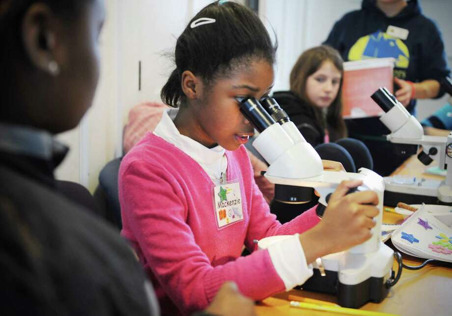 Mackenzie Moore (10) of Norwalk examines a hair sample during the final day of the week long SoundWaters Science Stars program in Stamford, Conn., where girls learn about science and discover career opportunities, first-hand, from women scientists. On Friday February 21, 2014 they spent the day on forensic science, using science equipment and the scientific methods to solve a mystery with clues such as fingerprints, fibers and handwriting samples. Photo: Dru Nadler / Stamford Advocate Freelance