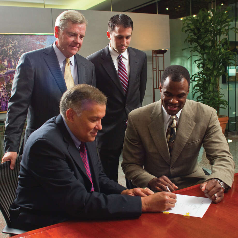 USAA President and CEO Joe Robles Jr., front left, signs a commercial real estate partnership agreement with former San Antonio Spurs player David Robinson, front right, as Pat Duncan, USAA Real Estate Co. chairman and CEO, back left, and Daniel Bassichis, RobinsonÕs business partner, look on. Photo: Karl Neal Gerber, COURTESY USAA / USAA 2010