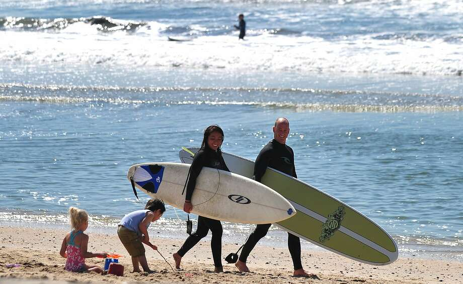 Surfers walk past children playing in the sand at Sunset Beach.  Californians are growing increasingly confident that better times are finally ahead, a new Field Poll indicates. Photo: Frederic J. Brown, AFP/Getty Images