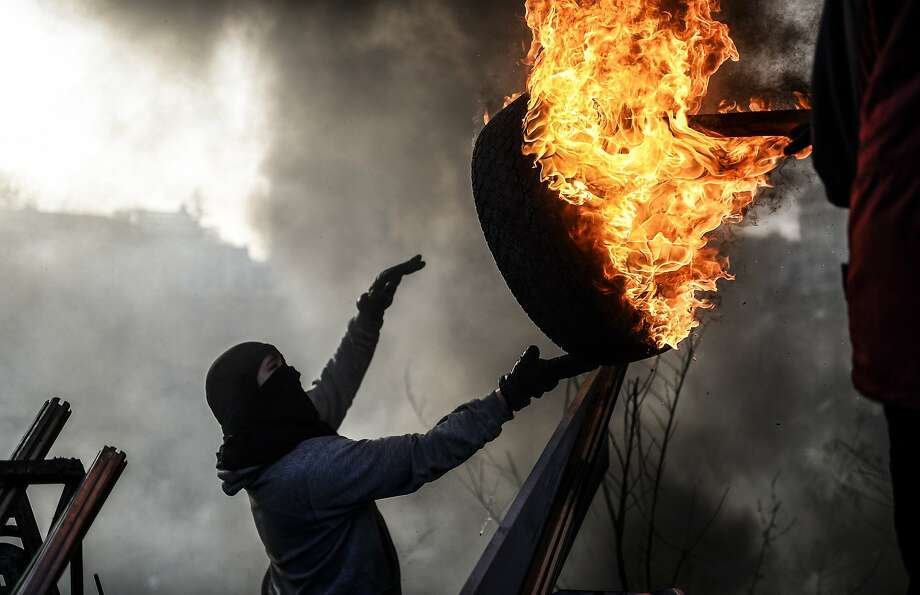 Hot wheels:An anti-government demonstrator tosses a burning tire as he builds a barricade in   Independent Square in Kiev. Ukraine's president and protest leaders struck a deal Friday to end the 3-month crisis in the capital. Photo: Bulent Kilic, AFP/Getty Images