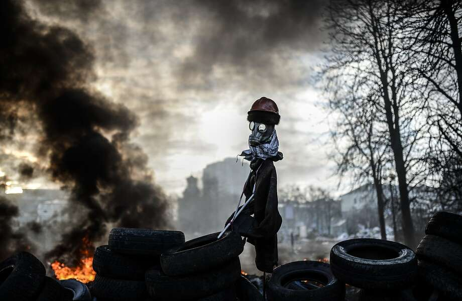 Scarecrow of the tire pile:An effigy guards a barricade separating civilians from government forces in Kiev. Photo: Bulent Kilic, AFP/Getty Images