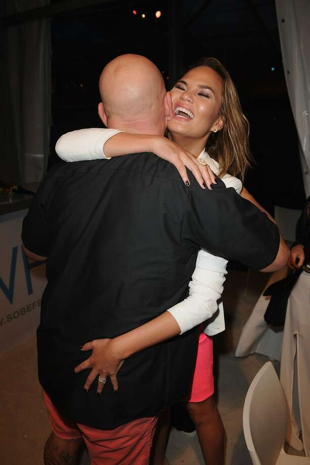 Is that an appetizer or entree?Sports Illustrated swimsuit model Chrissy Teigen samples   chef Michael Symon at Moet Hennessy's The Q during the Food Network South Beach Wine & Food   Festival in Miami Beach. Photo: Larry Marano, Getty Images