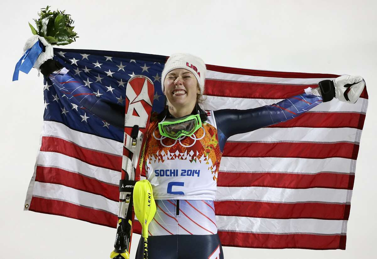 Women's slalom gold medal winner Mikaela Shiffrin of the United States poses for photographers with the U.S. flag at the Sochi 2014 Winter Olympics, Friday, Feb. 21, 2014, in Krasnaya Polyana, Russia.