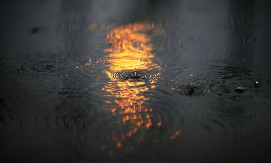 A rain drop falls in the reflection of the Olympic flame in a puddle at the 2014 Winter Olympics, Tuesday, Feb. 18, 2014, in Sochi, Russia.  Photo: David Goldman, Associated Press