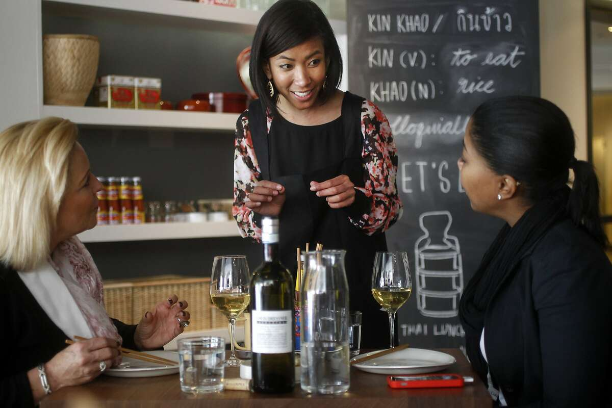 Paveena Jaicham (center) explains a dish to Adrienne Games (left) and Sabrina Brutus at Kin Khao, a new Thai restaurant by author and food blogger Pim Techamuanvivit.