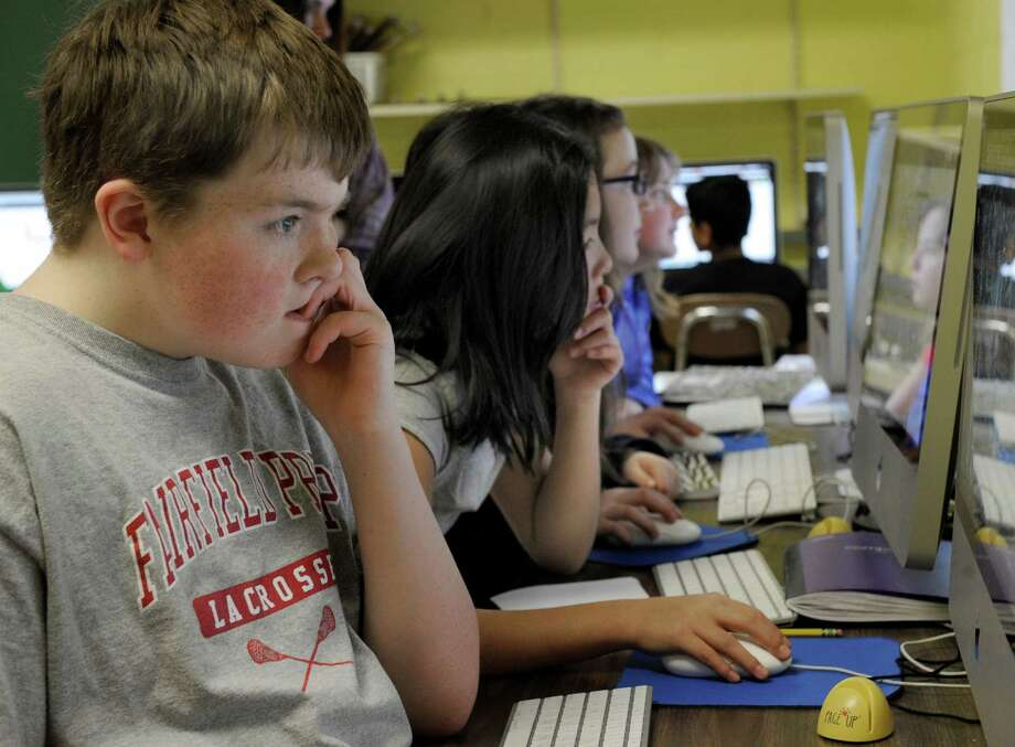Fifth-grader Matt Schlichtig, left, studies his computer screen during a training session Friday. Johnson School in Bethel, Conn. are giving kids training with computer skills necessary for the new state online tests, called Smarter Balanced Assessment, Friday, Feb. 21, 2014. Photo: Carol Kaliff / The News-Times