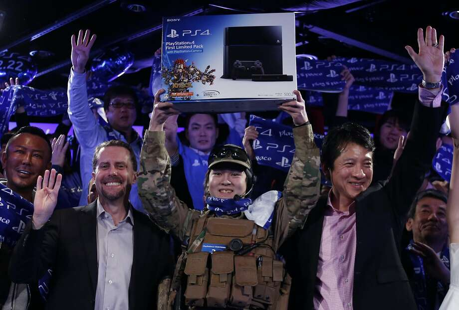 Ryo Watanabe, above, is the first customer in Japan to get a PlayStation 4 console. Other shoppers, including the woman below, snapped them up. Photo: Yuya Shino, Reuters